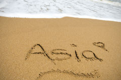 Asia writeen in sand on the waters edge Royalty Free Stock Photo