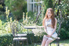 Asia young woman with flowers sitting on chair in park Royalty Free Stock Images