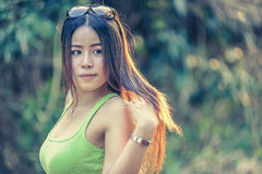 Asia young Woman wearing green vest, put her hair. Fasion of asia young Woman wearing green vest stand in park, put her hair, vintage effect Royalty Free Stock Images