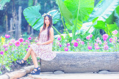 Asia young women sitting in colorful flower garden Stock Photos