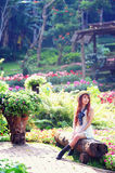 Asia young women sitting in colorful flower garden Royalty Free Stock Images