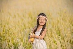 Asiagirl que joga a guitarra ao prado exterior na natureza imagem de stock