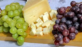 Asiago cheese and black grapes and white grape Royalty Free Stock Photography