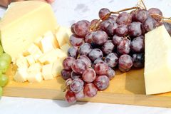 Asiago cheese and black grapes and white grape Stock Image