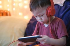 Free Asian 2 -3 Years Old Toddler Boy Child Listening To Music With Headphones From Smartphone, Kids Playing With Phone In Bedroom At H Royalty Free Stock Photography - 168659697