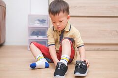 Free Asian 2 - 3 Years Old Toddler Boy Sitting And Concentrate On Putting On His Black Shoes / Sneakers Royalty Free Stock Image - 173064976