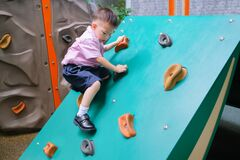 Free Asian 2 - 3 Years Old Toddler Child Having Fun Trying To Climb On Artificial Boulders At Schoolyard Playground, Little Boy Stock Image - 169031271