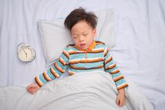 Free Asian 3 - 4 Years Old Toddler Boy Kid Taking A Nap, Sleeping On His Back With Alarm Clock, The Importance Of Sleep In Child Stock Photo - 174245490
