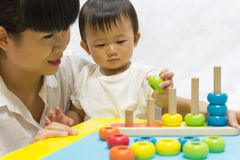 Asian adorable baby one year is playing color puzzle pyramid for Stock Photography