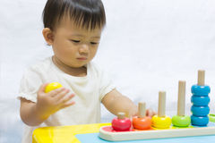 Asian adorable baby one year is playing colorful puzzle pyramid Royalty Free Stock Photo