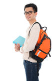 Asian adult male student. Handsome Asian adult student in casual wear with school bag carrying text books standing isolated on white background. Asian male model Royalty Free Stock Image