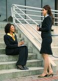 Asian And African American Businesswomen. Two businesswomen talking outdoor by stair. informal business discussion royalty free stock photos