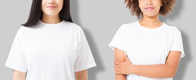Asian and african american girl in blank template t shirt isolated on gray background. Women in tshirt with copy space and mock up royalty free stock photography