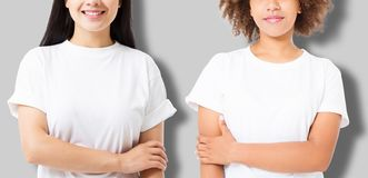 Asian and african american girl in blank template t shirt isolated on gray background. Women in tshirt with copy space and mock up royalty free stock photos