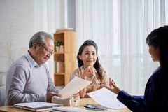 Consulting with estate agent. Asian aged couple meeting with real estate agent royalty free stock photos