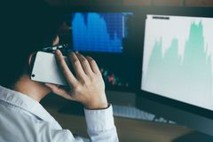 Asian agent trader man working and analysis in office and dealing with market financial charts and graphs and calling to customer.  royalty free stock image