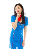 Asian air stewardess with finger on lips looking up Stock Image