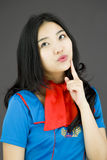Asian air stewardess looking up with finger on chin Royalty Free Stock Photography