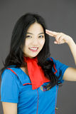 Asian air stewardess pointing finger to head and smiling Royalty Free Stock Photos