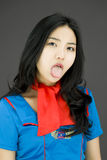 Asian air stewardess poking out tongue towards camera Royalty Free Stock Photo