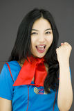 Asian air stewardess punches fist into the air isolated on colored background Royalty Free Stock Photography