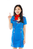 Asian air stewardess smiling and pointing upwards Royalty Free Stock Photography