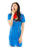Asian air stewardess yawning with hand over mouth Royalty Free Stock Photos