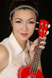 Asian Amerian teen girl protrait with a red ukulele Stock Photo