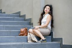 Asian American businesswoman crying alone sitting on street stairs suffering stress and depression crisis being victim of mobbing stock images