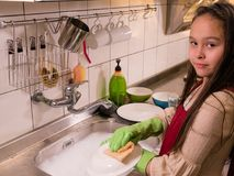 Asian  American girl washing dishes Royalty Free Stock Photo
