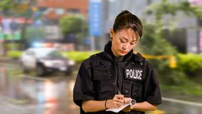 Asian American Police Officer at Crime scene Taking Notes royalty free stock images