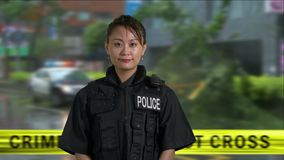 Asian American police officer at crime scene. Asian American woman police officer at crime scene stock footage