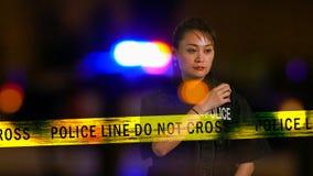 Asian American Policewoman using police radio Stock Image