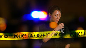 Asian American Policewoman using police radio Royalty Free Stock Photo