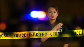 Asian American Policewoman using police radio. With siren and boundary tape in background, multiple exposure Royalty Free Stock Image