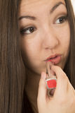 Asian American teen applying red lipstick portrait close up Royalty Free Stock Image