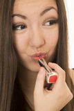 Asian American teen applying red lipstick to her puckered lips Stock Photography