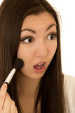 Asian American teen girl applying blush on her cheeks Stock Images