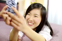 Asian american woman in bed taking selfie smiling Stock Images