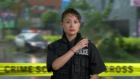 Asian American police officer at crime scene. Asian American woman police officer at crime scene on cb radio stock footage
