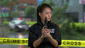 Asian American woman police officer at crime scene. Holding pistol firearm stock video