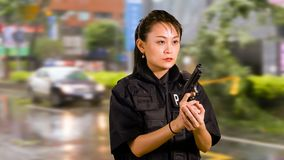 Asian American Woman Police Officer Holding Pistol stock photography