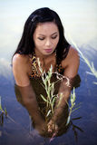 Asian American Woman In River Holding Plant Royalty Free Stock Photo