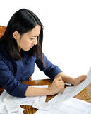 Asian American woman working on taxes. Beautiful young Asian American woman working on her paper tax returns royalty free stock image