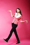 Asian Amusing Teenager Walking in Pink Studio Stock Photo