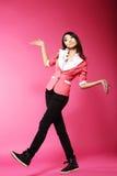 Asian Amusing Teenager Walking in Pink Studio stock photo