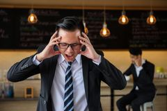 Asian angry and stress businessman screaming. And holding his head while another men talking business plan on smartphone at coffee cafe. Contrast feeling of Royalty Free Stock Photos
