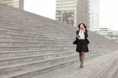 Asian appearance business woman walk along stairs speaking. Asian appearance business woman walk along broad stairs by and smiling speaking by phone. In hand stock photo