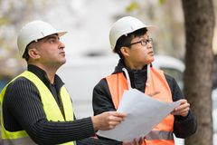 Asian apprentice engineer at work on construction site with the senior manager. Young Asian trainee engineer at work on construction site with the senior manager Royalty Free Stock Images