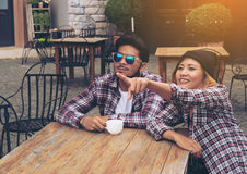 Asian and Arabic students couple in cafe Stock Photo